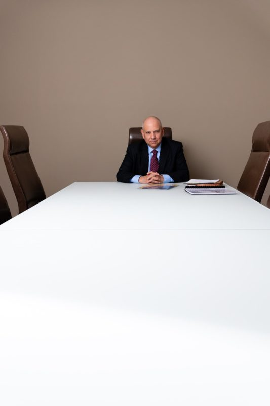 Even if a client is already impressive, and the office is impressive, I have to do everything I can to make the client look larger than life. That's why I try to frame and compose a scene in unique ways. In this scene, I framed the client at the end of a very long conference table, as if it's a scene from The Apprentice.